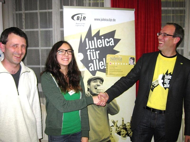 Einen Geldpreis erhielt die BDKJ-Delegierte Laura Frau für die Aktivitäten ihres Verbandes bei der Juleica. Udo Schoberth (Vorsitzender SJR Bamberg – links) überreicht den Preis unter Applaus des BJR-Referenten Martin Holzner.