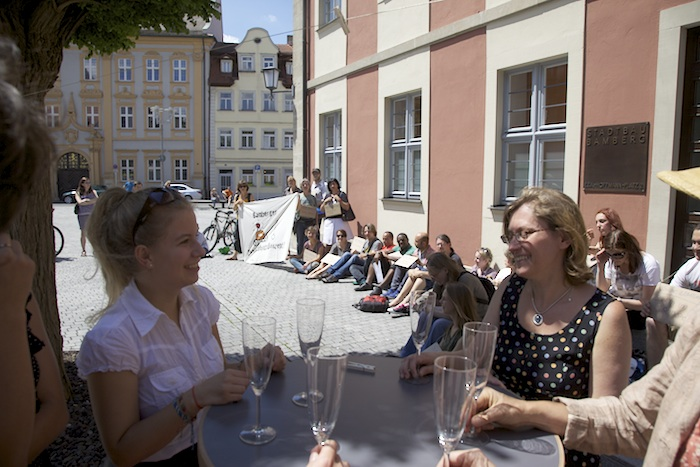 Die hinteren warten ohne Sekt oder Selters. Flashmob vor dem Verwaltungsgebäude der Stadtbau am Schillerplatz. Foto: Erich Weiß
