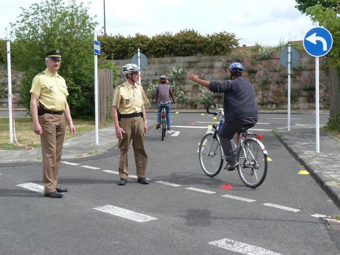 POK Franz Werner beim Fahrradunterricht mit den Asylbewerbern. Im Vordergrund ist der Dienststellenleiter der PI Bamberg-Stadt, Ltd. PD Udo Skrzypczak, zu sehen, der die Ausbildung wohlwollend unterstützte. Foto: Polizei