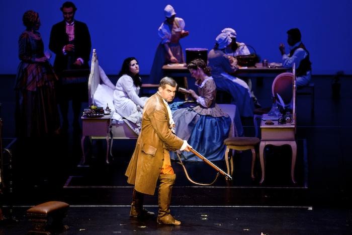 """In den lebenden Bildern zu Beginn der Nürnberger """"Figaro""""-Inszenierung zieht der Titelheld (Nicolai Karnolsky) grimmig mit einer mächtigen Büchse durchs Schloss. Kein Wunder, denn schließlich will der Graf vor Figaros Hochzeit schnell noch die Braut entjungfern. Foto: Ludwig Olah"""